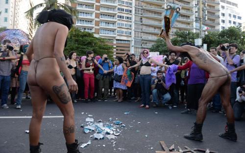 Manifestantes quebrando imagens sacras